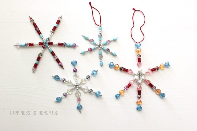 An image of four beaded snowflake decorations of different colours and sizes.