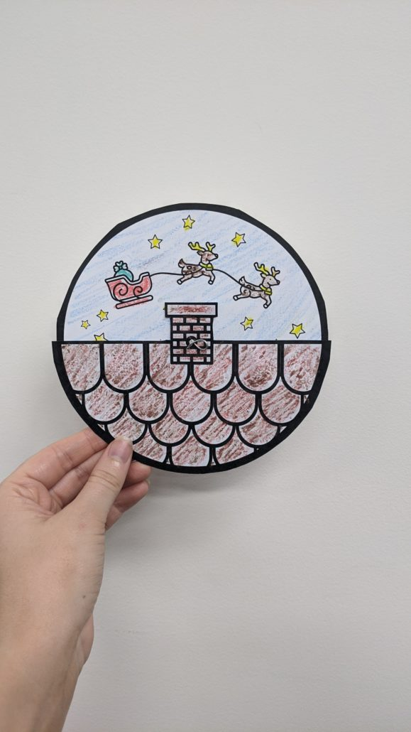 An image of a circle spinner. There is a tile roof and a sleigh and reindeer riding over the top.